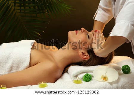 Portrait of beautiful woman taking head massage on green background
