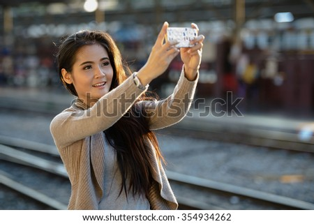 Portrait of beautiful woman taking selfie picture with mobile phone at train station