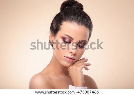 Portrait of beautiful woman touching her face, isolated on beige background.
