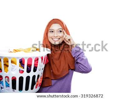 portrait of beautiful woman wearing hijab carrying laundry basket with hand in her heads pretend to thinking with copy space isolated on white - stock photo