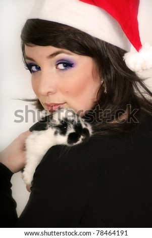 Portrait of beautiful woman wearing santa hat with black white rabbit