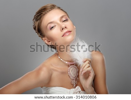 Portrait of Beautiful Woman Wedding Model on Grey Background. Advertising and Commercial Design. Shopping. Jewelry - Bridal necklace, Hairstyle. Girl with a necklace and a feather - stock photo