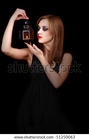 Portrait of beautiful woman-witch on black background - stock photo
