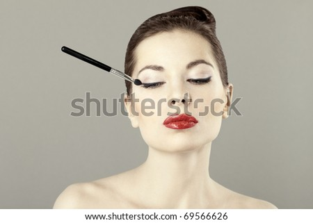 Portrait of beautiful woman with a brush for eyeshadow, doing makeup - stock photo