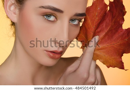 portrait of beautiful woman with autumn leaves on yellow background