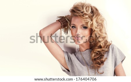Portrait of beautiful woman with bright fashion makeup, curly long hair and jewelry. Girl looking away. - stock photo