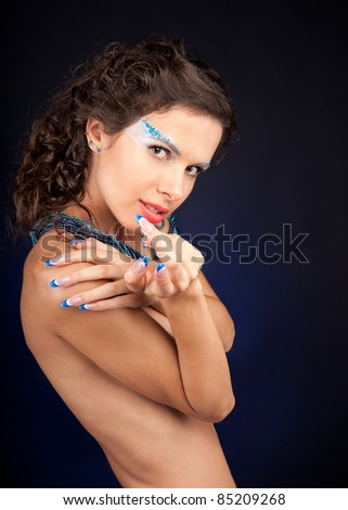 Portrait of beautiful woman with carly dark hair and shells in hands - stock photo