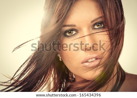Portrait of beautiful woman with flying hair, against light, isolated - stock photo