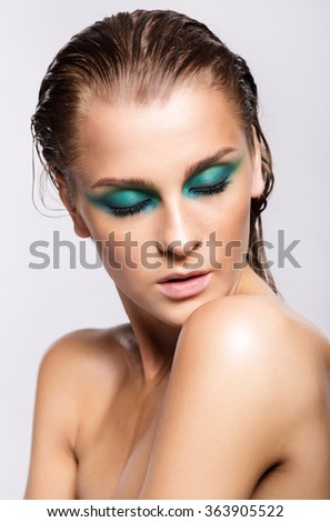 Portrait of beautiful woman with green wet shining makeup and closed eyes