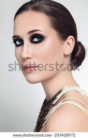 Portrait of beautiful woman with hair bun and smoky eyes - stock photo