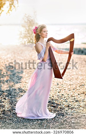Portrait of beautiful woman with harp - stock photo