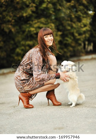 Portrait of beautiful woman with her little dog having good time in a autumn park  - stock photo