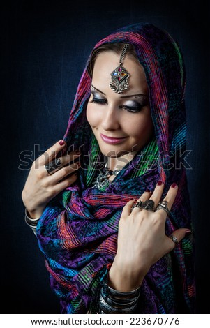 Portrait of beautiful woman with Indian tikka wrapped in scarf - stock photo