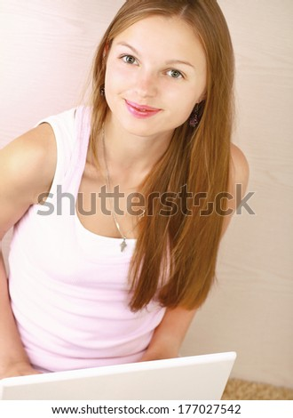 Portrait of beautiful woman with laptop sitting on the floor - stock photo