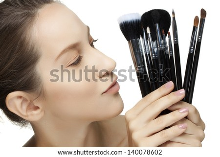 portrait of beautiful woman with make-up brushes, isolated on white background