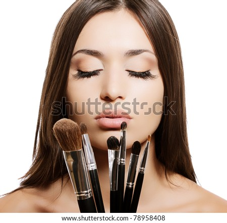 portrait of beautiful woman with makeup brushes - stock photo
