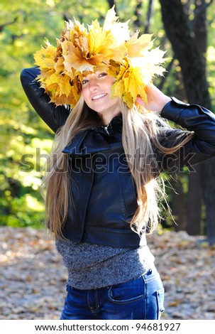 Portrait of beautiful woman with maple wreath - stock photo
