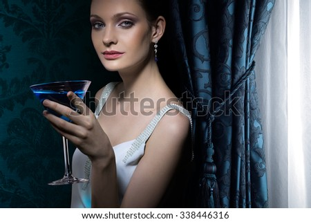 Portrait of beautiful woman with martini glass - stock photo