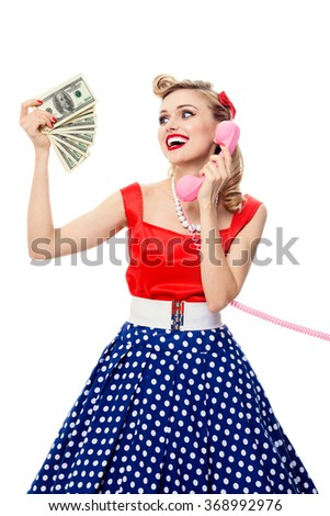 Portrait of beautiful woman with money, talking on phone, dressed in pin-up style dress in polka dot, isolated. Caucasian blond model posing in retro fashion and vintage concept studio shoot.