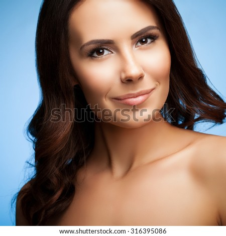 portrait of beautiful woman with naked shoulders, on bright blue background