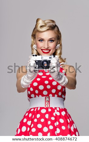 Portrait of beautiful woman, with no-name old film camera, taking picture, dressed in pin-up style. Caucasian blond model posing in retro fashion and vintage concept studio shoot, on grey background. - stock photo