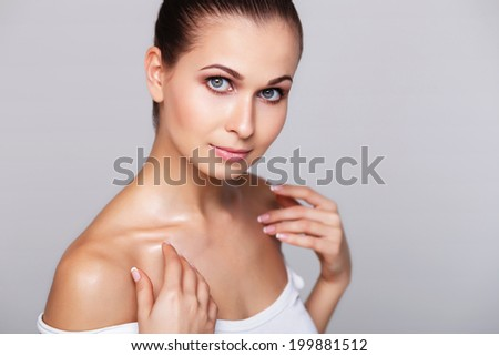 Portrait of beautiful woman with perfect skin on grey background - stock photo