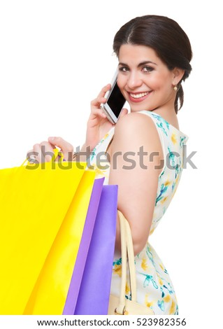 Portrait of beautiful  woman with shopping bags and cell phone.