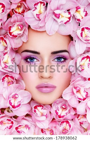 Portrait of beautiful woman with stylish make-up and pink orchids around her face - stock photo