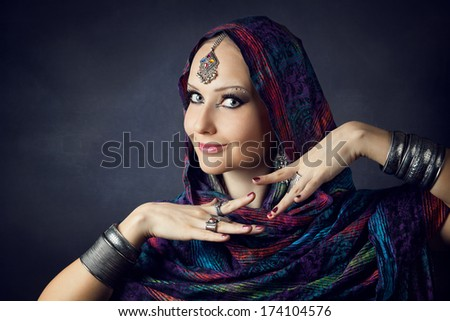 Portrait of beautiful woman wrapped in scarf - stock photo