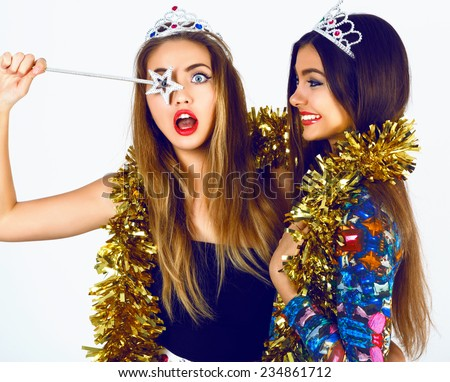 Portrait of beautiful women friends wearing bright sexy outfits, funny fake crowns  tinsel and magic want, ready for celebrating holidays party. having fun together and making funny faces. - stock photo
