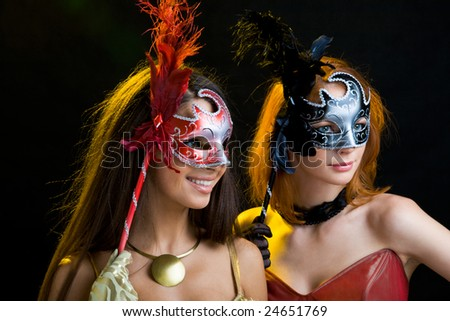 Portrait of beautiful women in masks over black background - stock photo