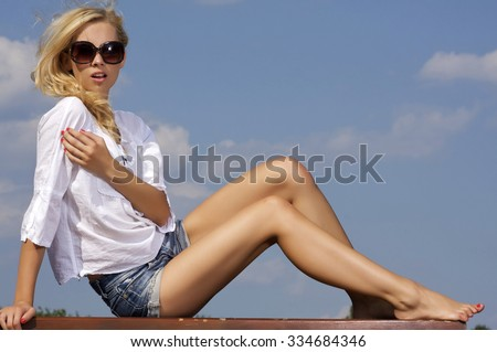 Portrait of beautiful young adult attractive sexy and sensuality pretty blonde girl in sunglasses and white shirt on background blue sky - stock photo