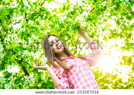 portrait of beautiful young adult brown long hair woman standing near the apple tree on a warm summer sunny day against sun light sky green texture leaves background Copy space for inscription - stock photo