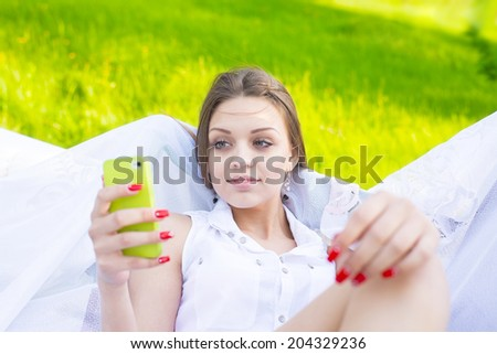 Portrait of Beautiful young adult caucasian woman reading a message on mobile phone Cute slim girl looking at cell screen on summer fresh green grass background - stock photo