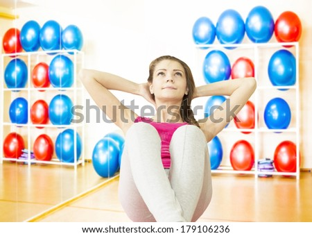 Portrait of Beautiful young adult cut girl exercising abdomen muscles in the gym while sit on big rubber ball.