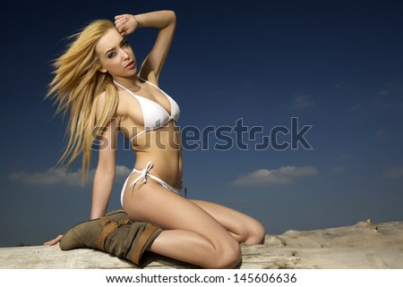 portrait of beautiful young adult sensuality and sexy attractive blonde woman in white bikini posing on the beach log