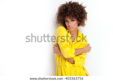 Portrait of beautiful young African American woman with afro and glamour makeup. Studio shot. Yellow fashionable dress. - stock photo