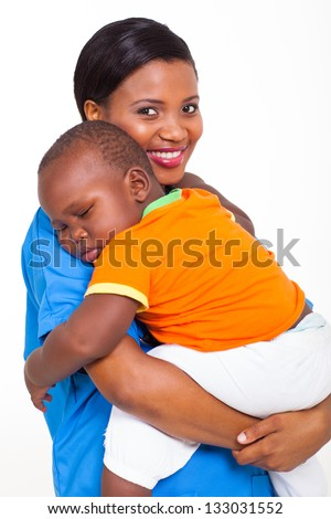 portrait of beautiful young african nurse carrying sleeping baby boy - stock photo