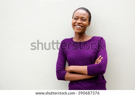 Portrait of beautiful young african woman standing with arms crossed against white wall - stock photo