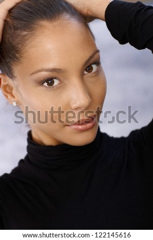 Portrait of beautiful young afro woman with hands in hair.