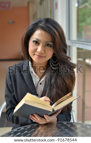 Portrait of beautiful young Asian business woman reading a book - stock photo