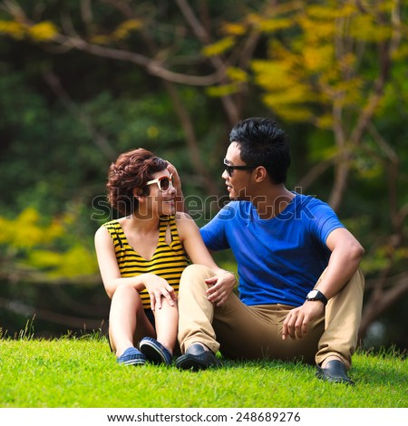Portrait of beautiful young asian couple sitting on ground in park relaxing - stock photo