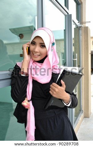 Portrait of beautiful young Asian Muslim business woman talking on the mobile phone while holding a laptop