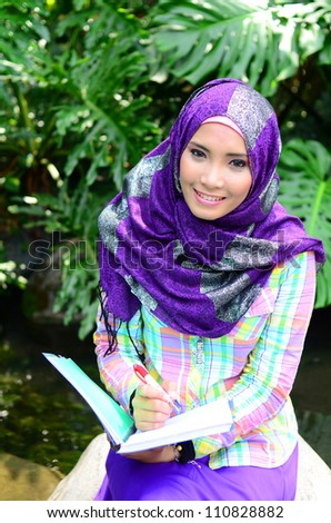 Portrait of beautiful young Asian Muslim was reading and writting a book at garden