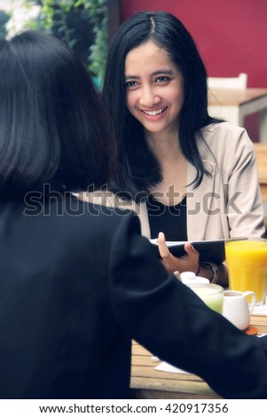 Portrait of beautiful young Asian urban women having a casual business meeting in an outdoors restaurant