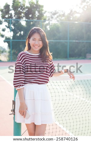 portrait of beautiful young asian woman wearing white clothes skirt in tennis course with happy face - stock photo