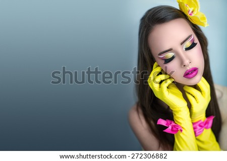 Portrait of beautiful young attractive girl, woman, lady, doll, Barbie, actress, model, dancer. Theater, club, party, disco. Perfect makeup, bright colors, yellow, pink, long eyelashes, pink lips.  - stock photo