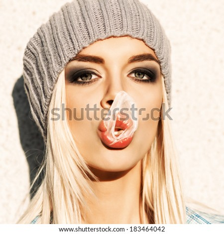 Portrait of beautiful young blond girl in beanie hat with her blown up bubble gum on her nose and plump lips - stock photo