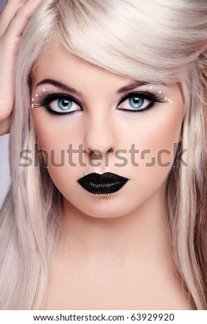 Portrait of beautiful young blond girl with fancy black make-up and piercing