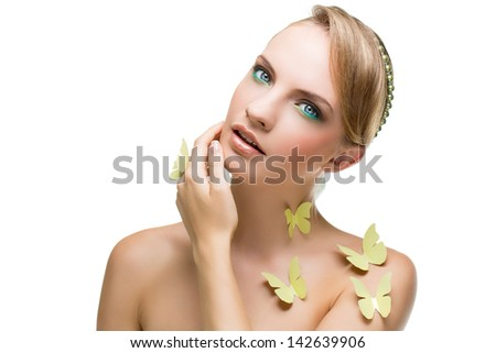 Portrait of beautiful young blond girl with green paper butterflies
